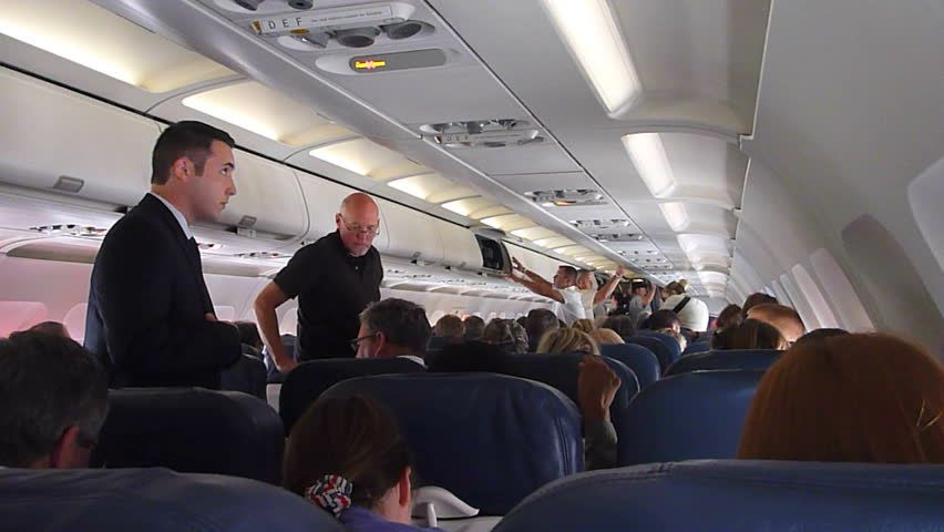 US AIRWAYS INTERIOR FLIGHT - CIRCA 2013:Interior airplane, point of view as passenger from coach seats as travelers depart plane.