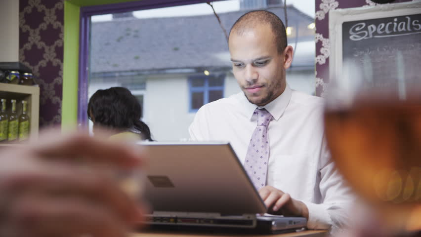 Attractive mixed race young professional male working or social networking, on a laptop computer in a cafe or coffee shop. In slow motion.