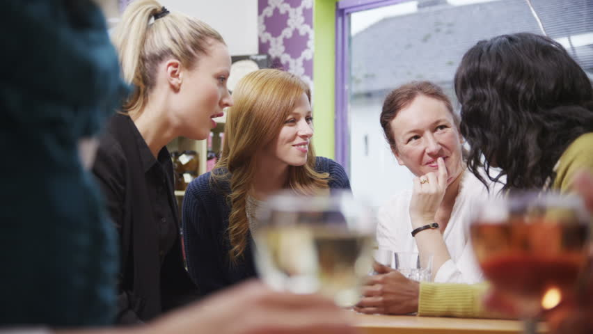 Happy and attractive group of female friends chatting and laughing together in a small cafe or wine bar. In slow motion.