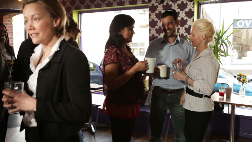 Drinks and a chat for networking city workers. A relaxed cafe or restaurant setting where colleagues discuss business.