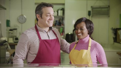 Portrait of happy mixed race couple or business partners, at work behind the counter of a delicatessen grocery store.