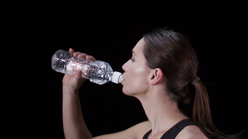 Slow motion sports woman drinking bottled water as she runs. Shot on RED Epic at 240 FPS