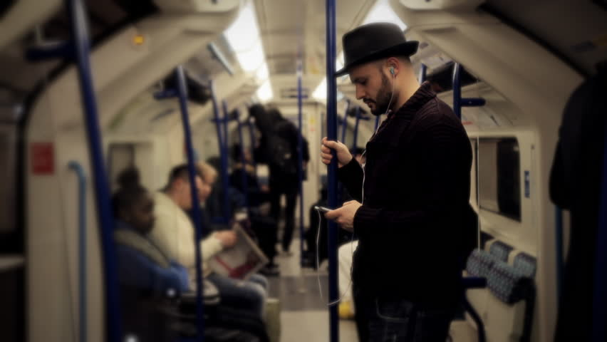 man listening music on a tube train standing wider shot