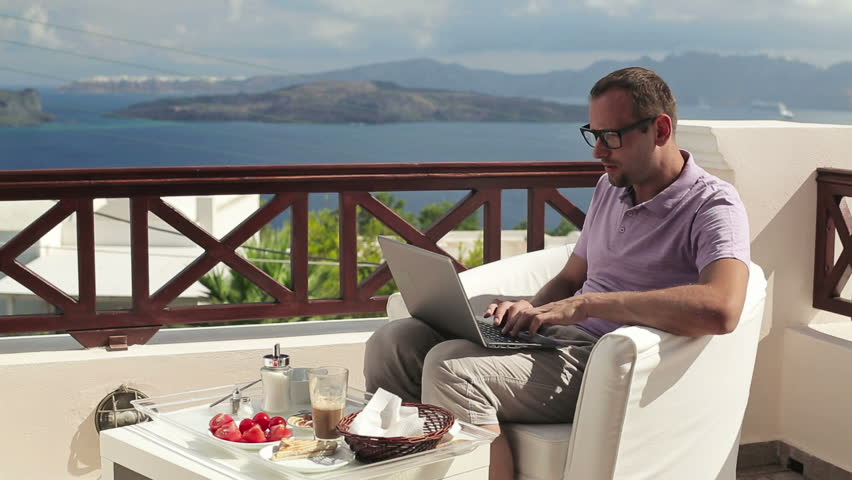Young man with laptop during breakfast on terrace