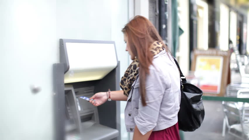 Girl takes money out of an ATM
