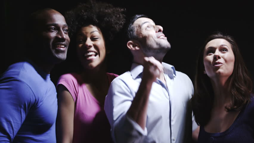 Group of attractive young people of various ethnic origins cheering against a black background.