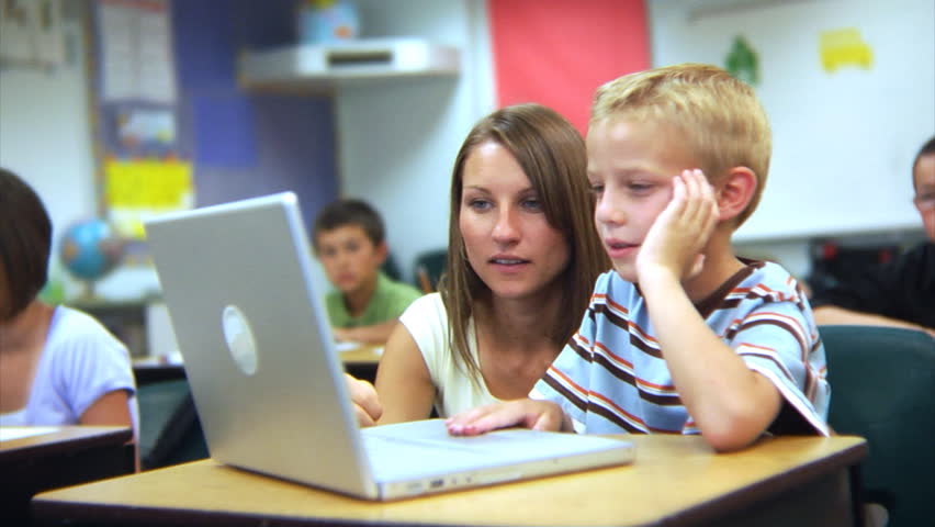 Elementary school student and teacher look at computer | Shutterstock HD Video #4541270