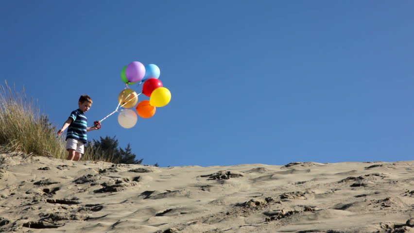 Boy running on sand dune with balloons