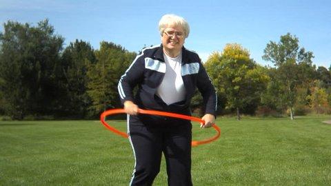 Senior woman at park playing with hula hoop