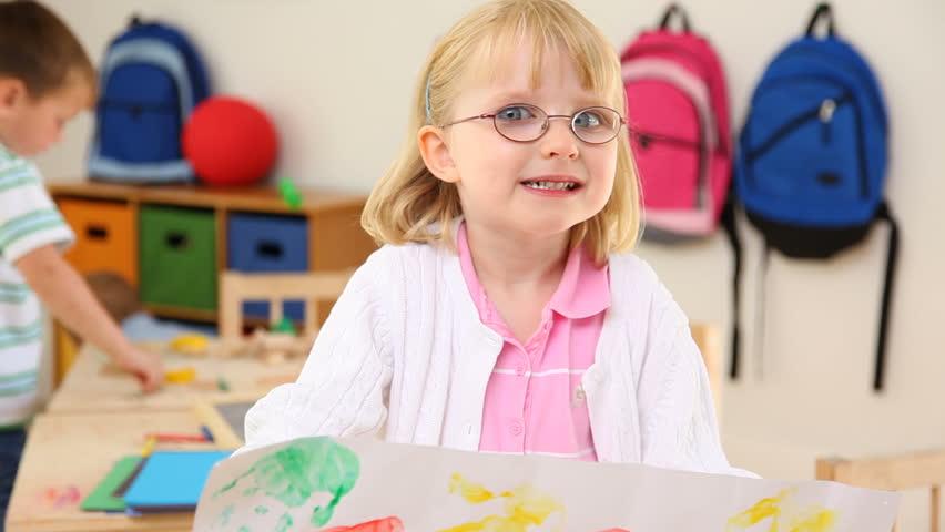Preschool child holding up painting