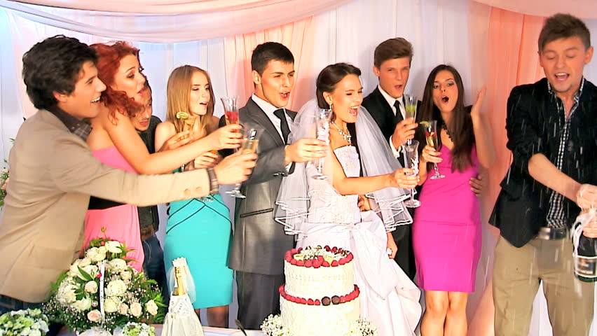 Group people at wedding table open bottle of champagne