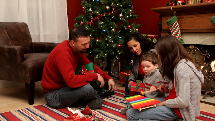 family by christmas tree playing with toys