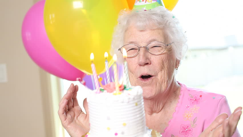 Senior woman blows out candles