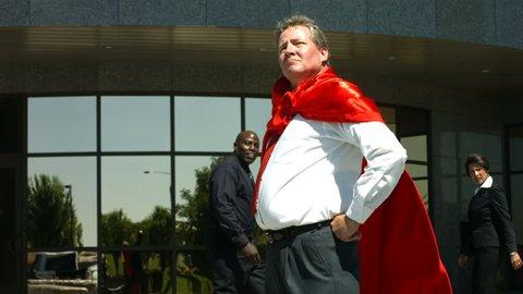 Businessman wearing superhero cape