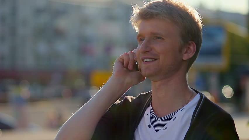 Man talking over phone, enjoying conversation, smiling, city