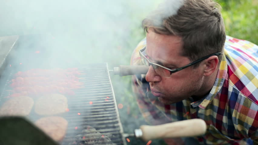 Man burning up grill in the garden