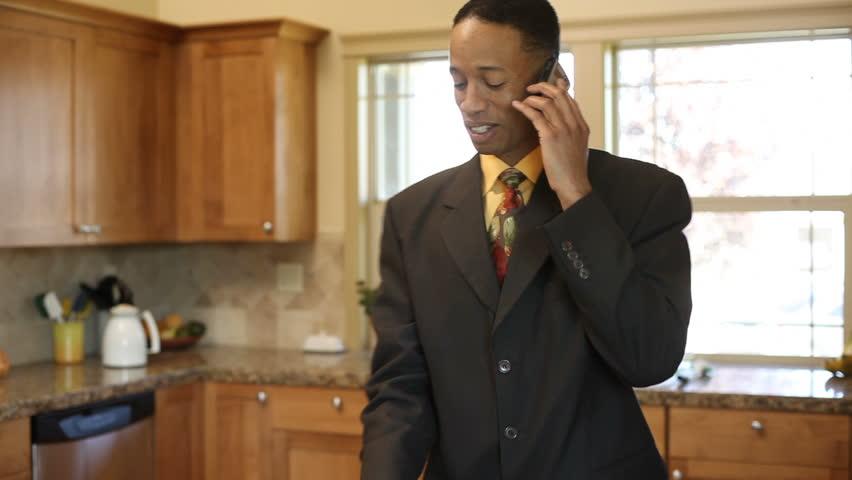 Businessman in kitchen talking on phone