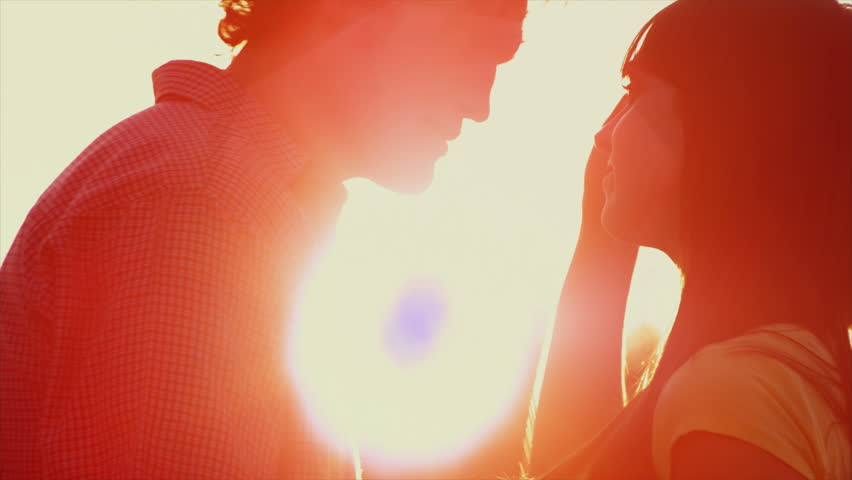 Beautiful Young Couple in Love kiss in a silhouette