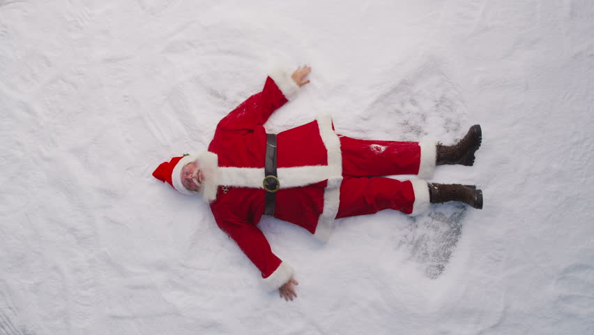 High angle shot of Santa Claus making a snow angel