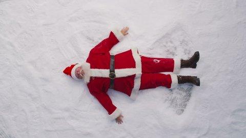 High angle shot of Santa Claus making a snow angel
