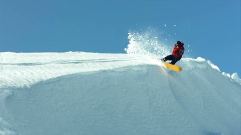 Snowboarder carves snow bank, super slow motion
