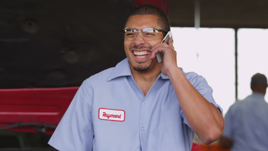 Auto mechanic talking on cell phone