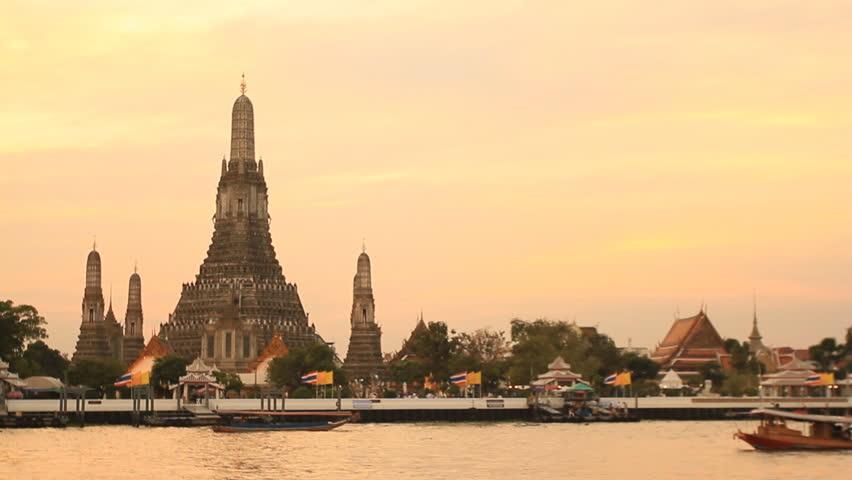 Twilight view of Wat Arun across Chao Phraya River during sunset in Bangkok, Thailand