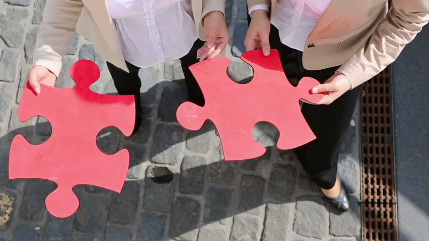 Hands of two business women holding two oversized red jigsaw puzzle pieces