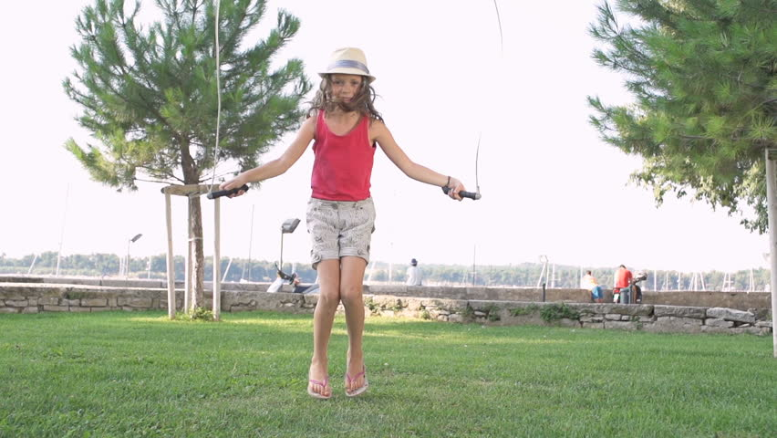 Slow Motion Shot Of A Cute Girl Wearing A Fashion Hat And Jumping Rope Outdoors.