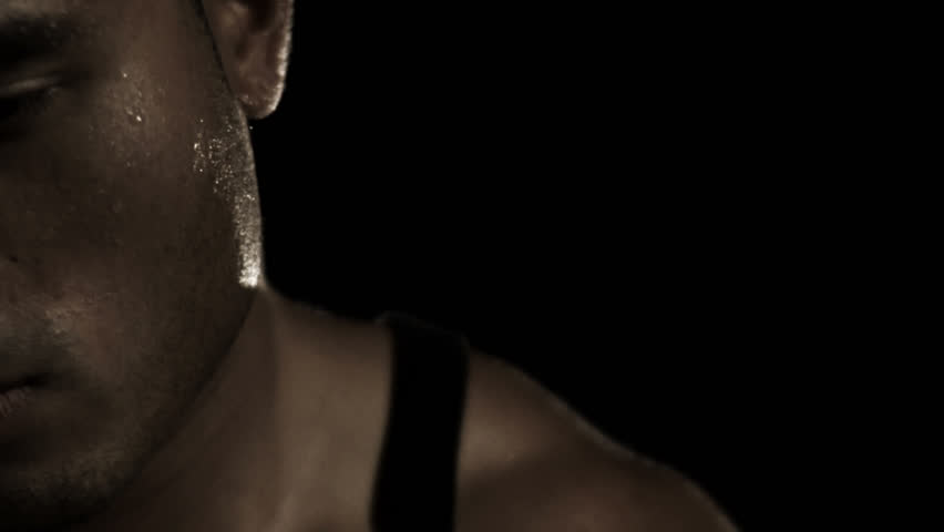 An ethnic male athlete breathes heavy and sweats after an intense exercise while staring hard into the camera in a dark gym, close up portrait
