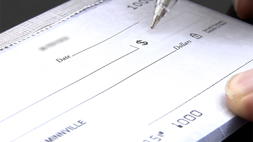 Close up of check being signed