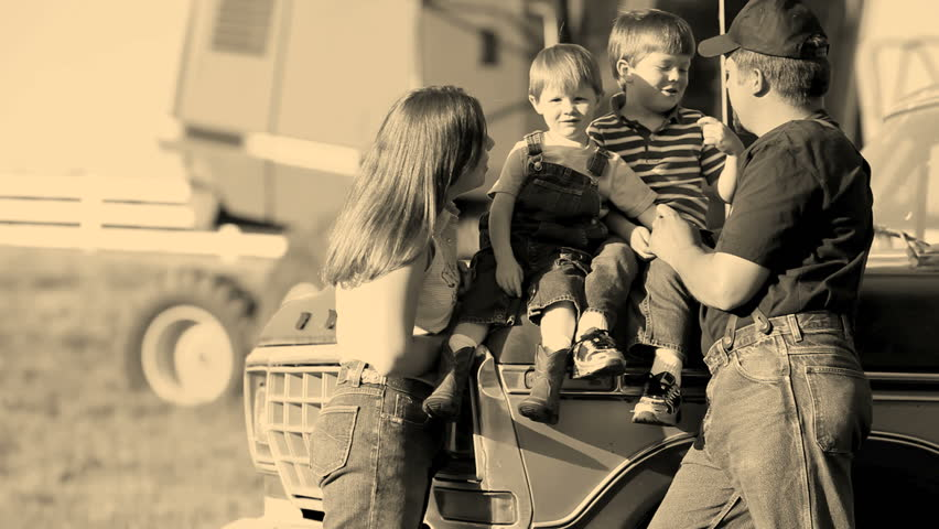 Family sitting by tractor on farm. Sepia effect.