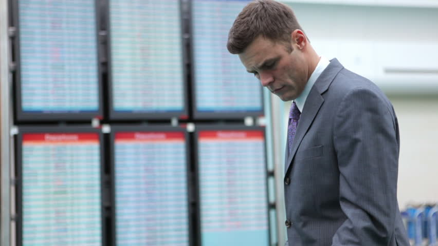 Business man at airport checks airline departure screens