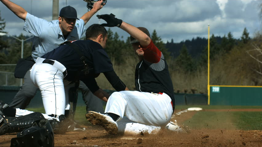 Baseball player slides is safe at home plate, slow motion