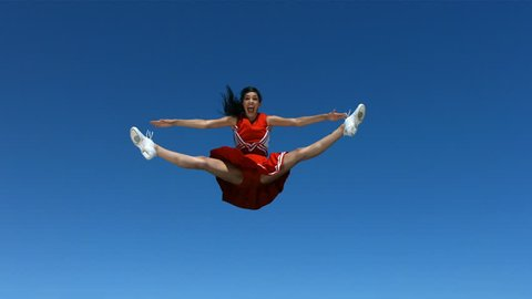 Cheerleader flies into air and does splits, slow motion