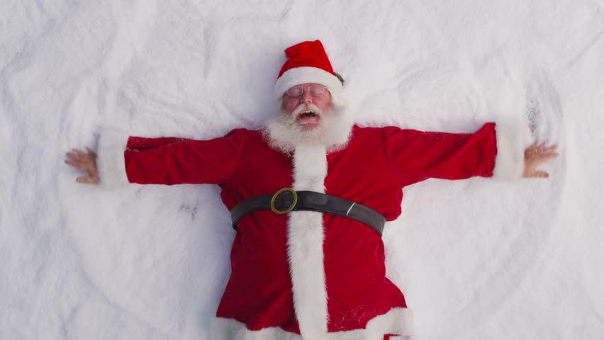 Santa playing in the snow. Overheard shot.