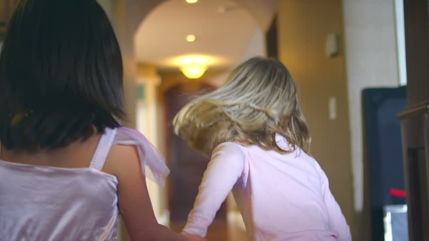 Two adorable young girls hold hands as they dance through the hallway together. Medium slow motion dolly shot.