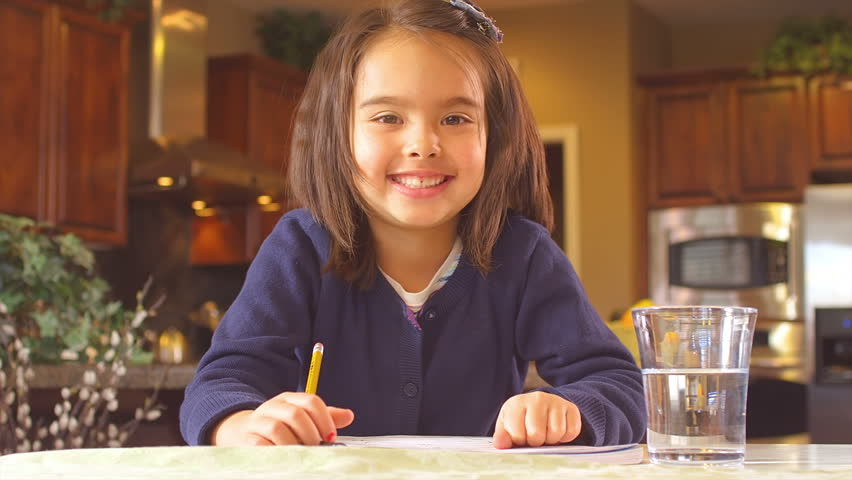 A funny little girl sits at the table and does her homework, then looks up and gives the camera a thumbs up and a thumbs down. Close up shot.   Shutterstock HD Video #4659080