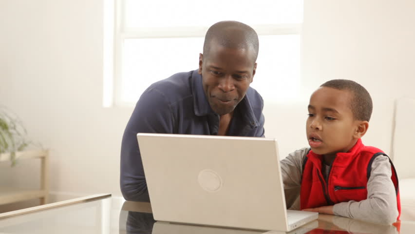 Portrait of African American father and son with laptop