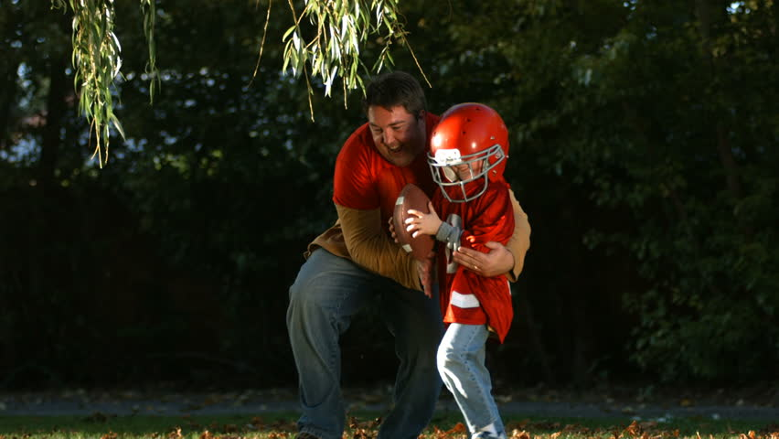 Football players, father and son, Family playing in autumn leaves together