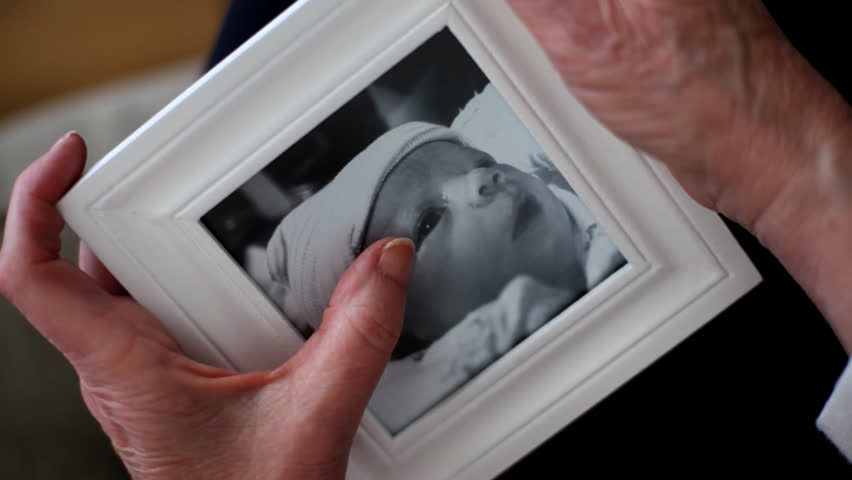 Grandmother holds framed photo of baby