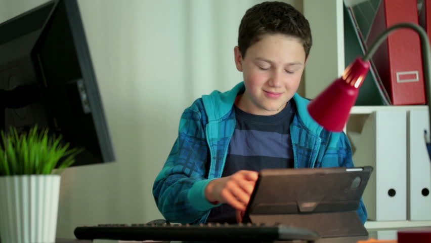 Young boy with tablet computer in home