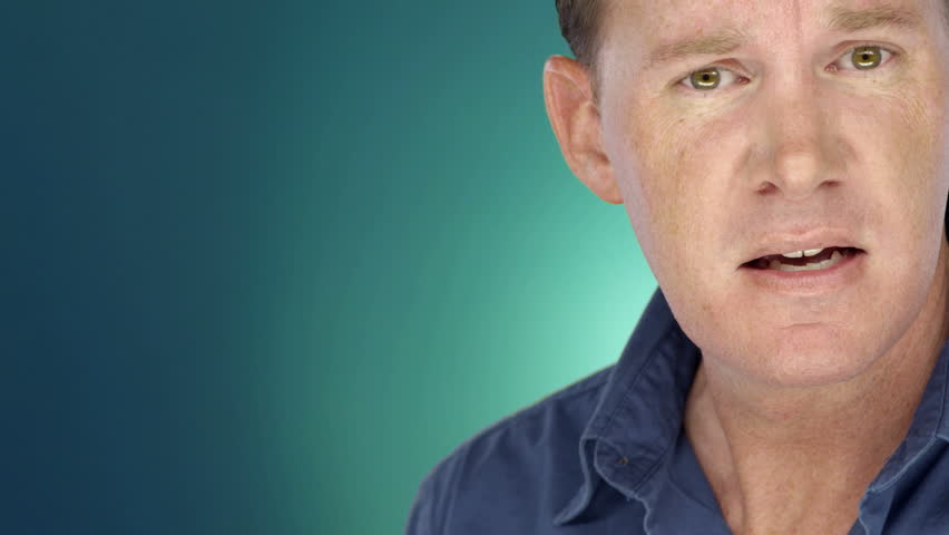 Man on blue-green background looks into the camera with an upset expression. Close up shot.