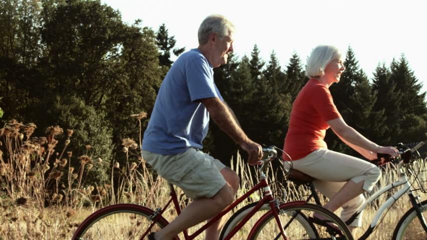 Senior couple enjoy time together bike riding. Wide shot. | Shutterstock HD Video #4682057
