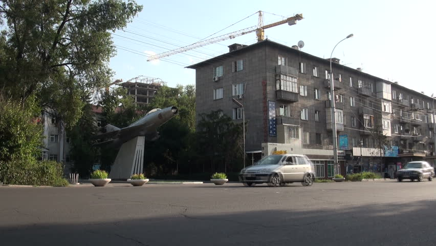 BISHKEK, KYRGYZSTAN - 28 JULY 2013: Cars drive past an old MiG fighter jet, in the streets of Bishkek, capital of Kyrgyzstan