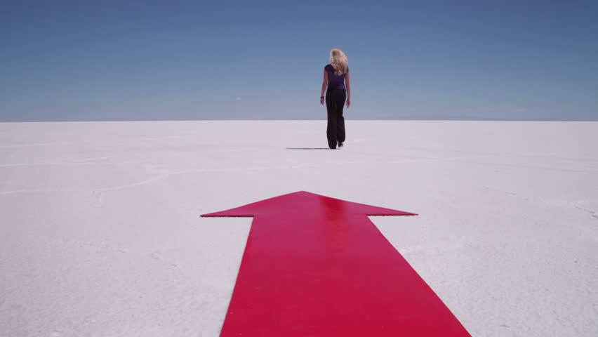 Businesswoman walks by red arrow at salt flat