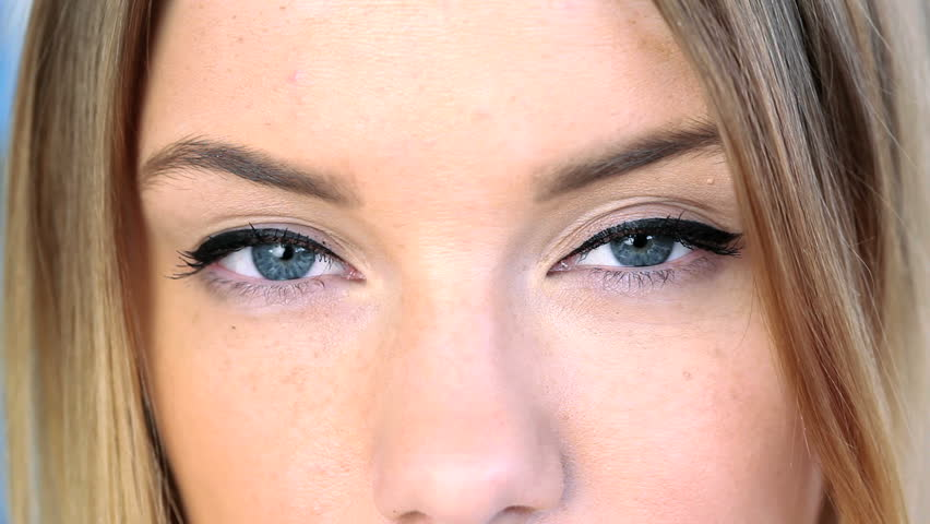 Close up on blonde woman's blue eyes looking at camera
