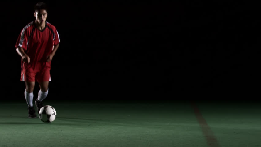 A soccer player runs up to the camera and then kicks the ball out of frame