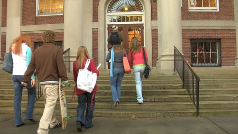 Group of college students walk into building
