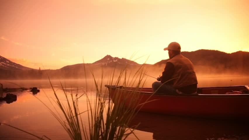 Man fishing in lake at sunrise